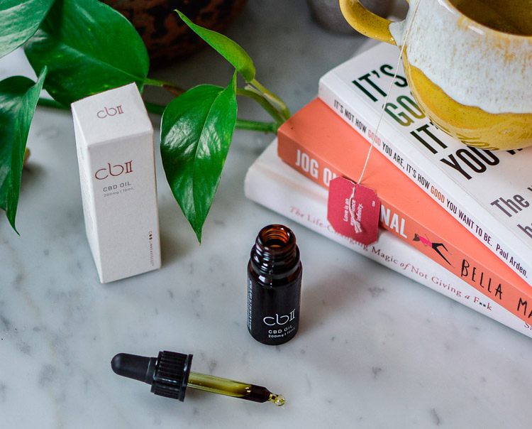 CBD oil, plants and books on a table to reduce stress